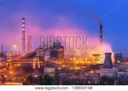 Metallurgical plant at night. Steel factory with smokestacks . Steelworks iron works. Heavy industry in Europe. Air pollution from smokestacks ecology problems. Industrial landscape at twilight