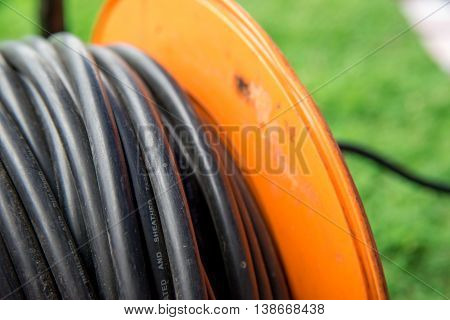 Close-up detail of a reel of electrical extension cable on a grass field at an outdoor event.