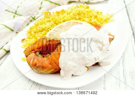 Pink salmon with lemon, milk sauce and rice with turmeric in a dish, kitchen towel on a background of wooden boards