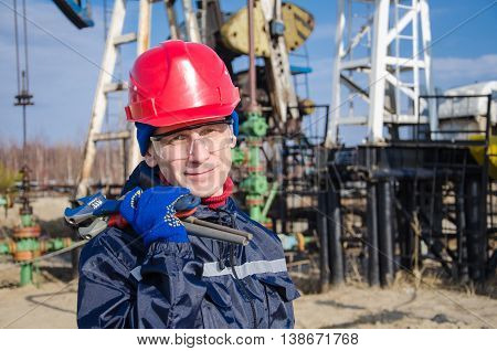 Portrait of man engineer in the oil field wearing red helmet and work clothes holding wrenches in his hand. Blurry pump jack and wellhead background. Oil and gas concept.