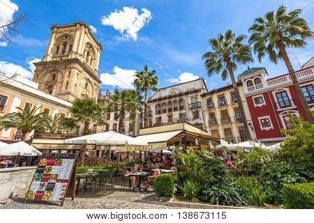 Granada, Andalucia, Spain - April 16, 2016: tourists eat at restaurant El Deseo in Plaza de las Romanillas. On background the Tower of Granada Cathedral in a sunny day.