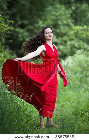 Beautiful young caucasian brunette woman in red dress outdoors whole-length portrait