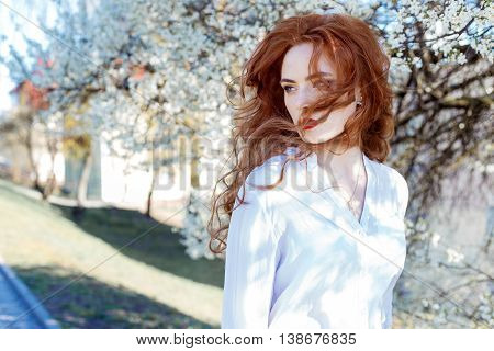 cute portrait of a beautiful redhead girl with make-up and red lipstick in a white shirt in the garden among the blooming trees on a sunny warm evening