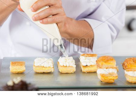 Chef decorating with a pastry bag with cream