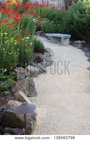 A curved garden path edged with stones winds through a perennial garden with crocosmia and dasies.
