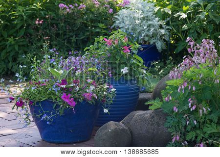 Bright blue pots overflow with colorful flowers in a shaded brick patio.