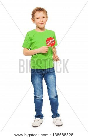 Full-length portrait of seven years old boy in green tee and denim, pointing to a small red Stop sign icon, isolated on white