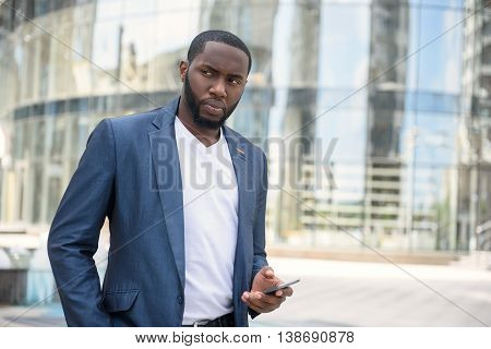 Serious young man is looking around with suspicion. He is standing near modern building and using mobile phone