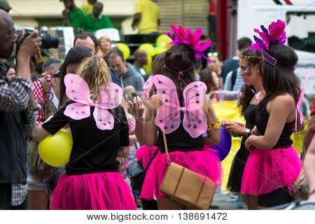 BATH SOMERSET UK - JULY 16 2016 Group of women in pink short skirts being photographed. Bath Carnival procession bringing a South American festival atmosphere to Somerset