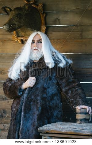 Brutal druid old man with long silver hair and beard holds wooden mug on stuffed boar head background
