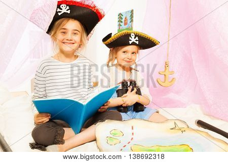 Two cute girls in tricorns playing pirates, reading fairy-tales about Treasure Island