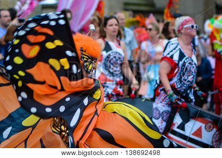 BATH SOMERSET UK - JULY 16 2016  Dancer in butterfly costume. Bath Carnival procession around the streets of the city of Bath bringing a South American festival atmosphere to Somerset
