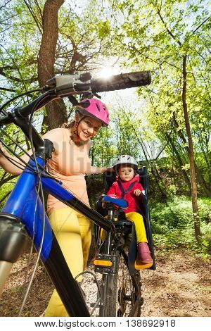 Sporty woman riding her little daughter in bicycle seat on forest trail