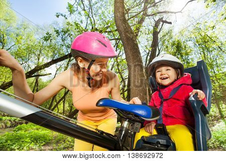 Close-up portrait of happy little girl in bike seat with her mother cycling through spring woodland