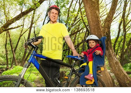 Sporty man riding his little daughter in bicycle seat in the sunny spring forest