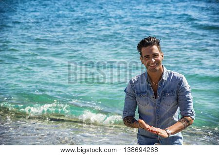 Handsome Athletic Young Man in Trendy Attire, on a Beach in a Sunny Summer Day, Looking At Camera, against Blue Sea Background.