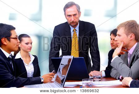 Businessman with four businesspeople at boardroom table in background