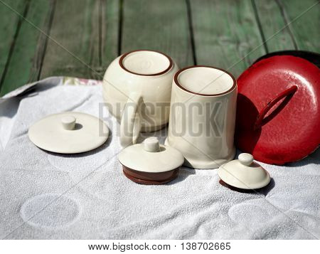 A bunch of upside down cups, casserole and tops drying  on a kitchen towel, outdoor closeup with selective focus