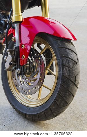 Closeup motorcycle wheels parked in a road.