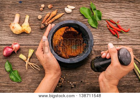 The Women hold pestle with mortar and spice red curry paste ingredient of thai popular food on rustic wooden background. Spices ingredients chilli pepper garlicgalanga lemongrass and kaffir lime leaves . poster