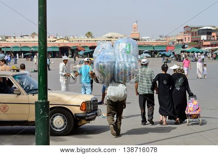 MARRAKESH - JULY 09: Unknown people walking at Djemaa el Fna square, July 09, 2013 in a Marrakesh, Morocco. The square is part of the UNESCO World Heritage.