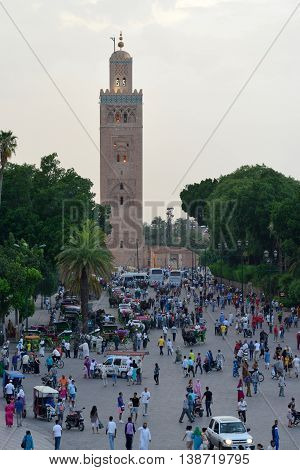 MARRAKESH - JULY 09: Unidentified people visit the Jemaa el Fna Square near Koutoubia Mosque, July 09, 2013 in a Marrakesh, Morocco. The square is part of the UNESCO World Heritage.