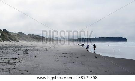 People walking along a misty beach in the morning