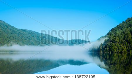 Misty lake in the forest with reflection