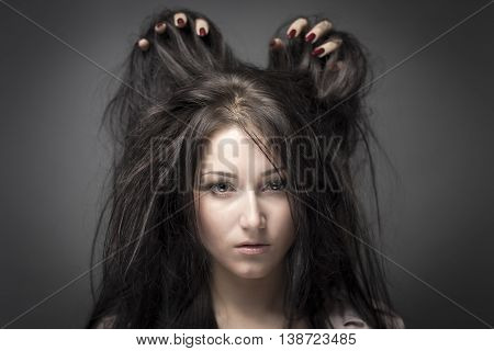 black-haired young female model A young woman with blue eyes on gray background