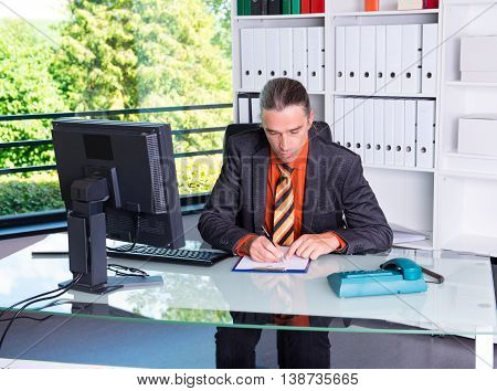 Young Business Man At His Desk Writing
