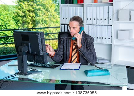 Young Business Man At His Desk And Calling