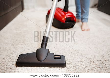 Image of female foot, red vacuum cleaner and black head of vacuum cleaner closeup