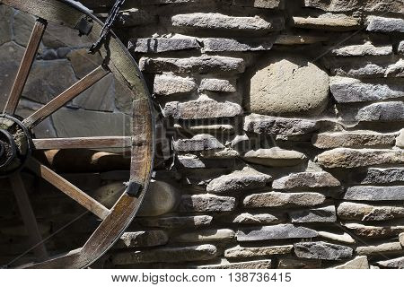 The old stonework with a wheel on a cart. Grunge background