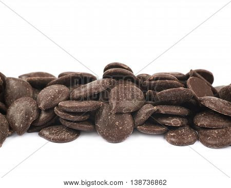 Line of cooking chocolate teardrop shaped chips isolated over the white background, close-up crop fragment