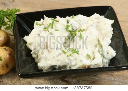 bowl of potato salad with chives and parsley