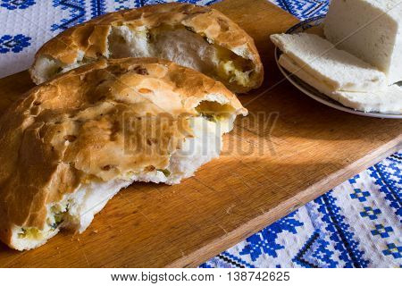 Slice Savoury pie with homemade cheese and greens on a cutting board on poltentse in ethnic style