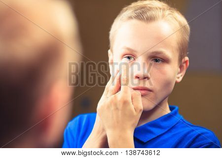 Shot of a young man trying to apply contact lenses in front of a mirror