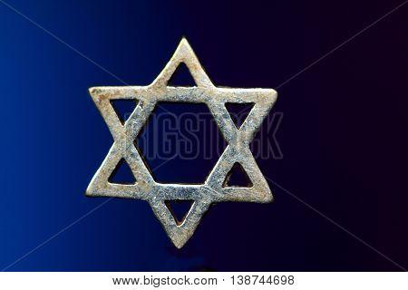 Silver Jewish star or Star of David against dark blue background