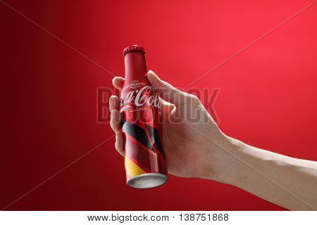 Kuala Lumpur,Malaysia 11th July 2016, Hand hold a bottle Coca-Cola limited edition of europe cup 2016 on red background. Coca Cola drinks are produced and manufactured by The Coca-Cola Company.
