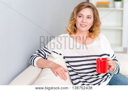 Joyful senior woman is drinking tea and smiling. She is sitting on couch and relaxing. Woman is looking forward with happiness