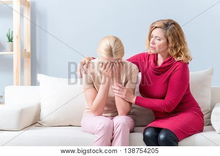 Do not cry my baby. Mature woman is consoling her daughter with worries. She is sitting on sofa and embracing her. Young girl is crying with desperation