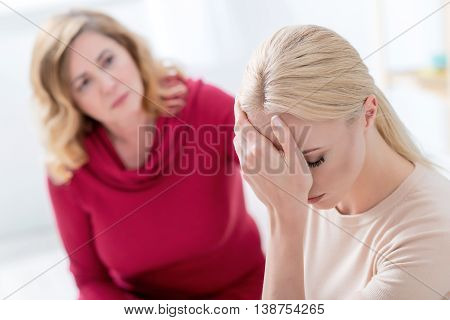 Desperate girl is telling about problems to her mother. She is crying and covering face sadly. Mature woman is consoling her daughter with worry