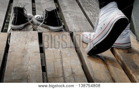 Teenager wearing white shoes standing behind black snickers on the wooden bridge, choice concept