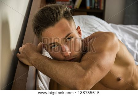 sexy young man with muscular body on bed