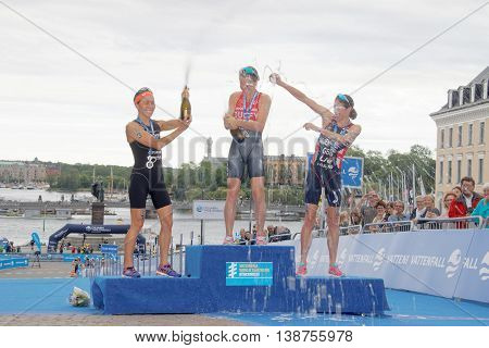 STOCKHOLM - JUL 02 2016: Flora Duffy Andrea Hewitt and Helen Jenkins laughing and squirting champagne on the winner's stand in the Women's ITU World Triathlon series event July 02 2016 in Stockholm Sweden