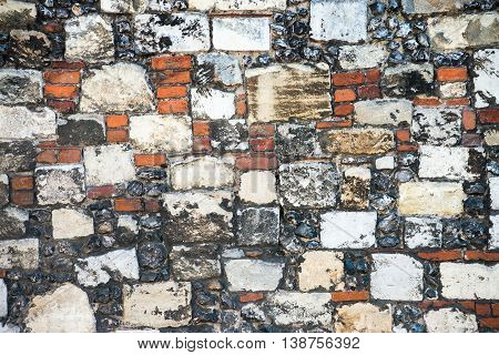Tradition old english historic wall built from flint red brick stone and rock ideal for texture or background.