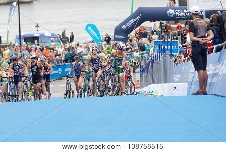 STOCKHOLM - JUL 02 2016: Group of triathletes running with cycles in the transition zone in the Women's ITU World Triathlon series event July 02 2016 in Stockholm Sweden