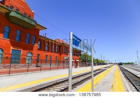 DODGE CITY, USA - MAY 17, 2015: Amtrak station of the city with platforms and tracks and the historic building as well as a modern sign in the back an engine and a rail tanker.
