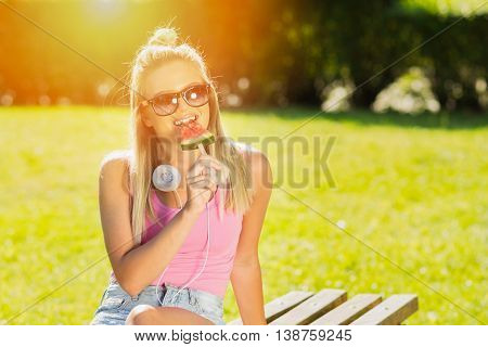 Young woman with in summer eating watermelon ice cream