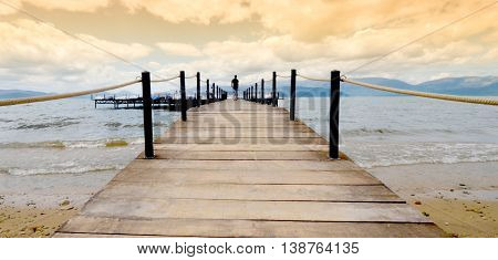 man walking on a pier on Lake Prespa,  Macedonia